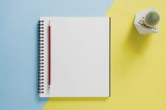 Minimales Konzept des Büroarbeitsplatzes Leeres Notizbuch, Kaktus, Bleistift Stockbilder
