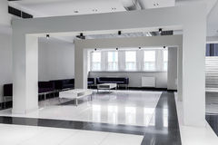 Minimalism that makes you concentrate on the forthcoming meeting. Airy minimalist waiting hall arranged in black and white with sofas and tables Royalty Free Stock Photography