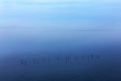 Minimalism. Seascape network of fishermen with the horizon line Royalty Free Stock Photo
