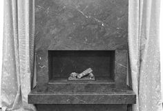 Minimalism stone fireplace. Apartment interior detail. Black white stock image