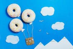 Minimalisme créatif de nourriture, beignet dans la forme de l'aérostat en ciel bleu avec des nuages, montagnes, vue supérieure, l Image stock