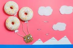 Minimalisme créatif de nourriture, beignet dans la forme de l'aérostat en ciel rose avec des nuages, montagnes, vue supérieure, l Photo stock