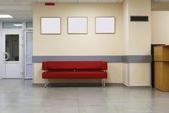 Minimalismo del estilo Sofá rojo, diseño interior, oficina Vacie la sala de espera con un sofá rojo moderno delante de la puerta  Imagen de archivo libre de regalías