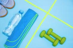 Minimalismo, teste di legno, scarpe da tennis, bottiglia di acqua, corda di salto, asciugamano, oggetti di sport fotografia stock