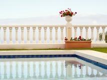 Minimalismus der Form und der Farbe, ein terassenförmig angelegter Leerraum mit einem weißen Topf mit dunkelroten Pelargonien geg lizenzfreie stockfotos