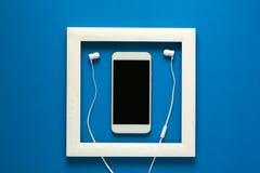 minimalismus Meisterwerk im Holzrahmen Smartphone mit Kopfhörern Technologie als Kunstkonzept lizenzfreie stockfotografie
