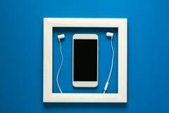 minimalismus Meisterwerk im Holzrahmen Smartphone mit Kopfhörern Technologie als Kunstkonzept stockfoto