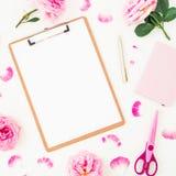 Minimalismusarbeitsplatz mit Klemmbrett, rosa Rosen, den Blumenblättern und Zubehör auf weißem Hintergrund Flache Lage, Draufsich Stockfoto