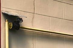 Minimalismusart Gelbes Gasrohr mit einem großen Hahn entlang der Backsteinmauer Alte Backsteinmauer Lizenzfreies Stockbild