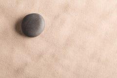 Minimalismuszenhintergrund mit schwarzem Stein im Sand lizenzfreie stockfotos
