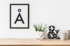 Minimalist poster and led light. A minimalist, aesthetic letter poster in a frame on a white wall above a led letter light and aloe in fabric planter Stock Photos