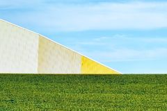 Minimalist Agriculture Abstract landscape. Minimalist agriculture abstract of a yellow metal cellar, spring green field and blue skies with light clouds Royalty Free Stock Image
