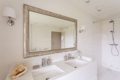Minimalist bathroom with large mirror. In a decorative frame and two marble sinks stock photo
