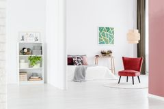 Minimalist bedroom with red chair. Minimalist bedroom with red, vintage chair and low ceiling lamp, separated by a curtain from the open space interior Stock Photos