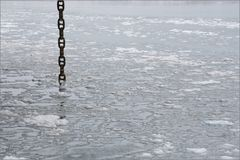 Minimalist Chain. Large chain, hanging downward into water Royalty Free Stock Photo