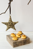 Minimalist Christmas and New Year decoration, rattan star hanging on a dry tree branch, coconut macaroons on a wood box Royalty Free Stock Photo