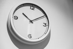 Minimalist Clock or Simple white clock hang on white wall. With space for text Royalty Free Stock Image