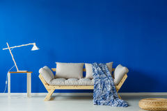 Minimalist day room with lamp. Minimalist day room with a modern lamp, and a patterned, blue blanket lying on the couch Royalty Free Stock Photos
