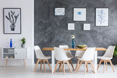 Minimalist dining room. Five simple paintings on concrete dark wall in minimalist dining room with designed chairs Royalty Free Stock Images