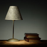 Minimalist lamp on wooden table with books Royalty Free Stock Photography