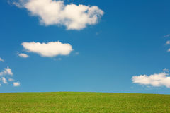 Minimalist Landscape with green field and cloudy blue sky Stock Image