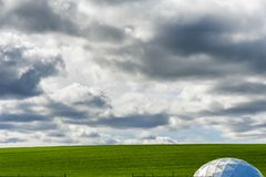 Minimalist farm ground under big sky. A minimalist landscape of green field under cloudy skies.  The top of a round dome greenhouse anchors the corner of the Royalty Free Stock Photography