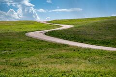 Free Minimalist Landscape Photo Of Prairie Grassland In Custer State Park With Blue Sky Clouds, As The Road Winds Through Royalty Free Stock Photos - 190837528