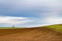 Minimalist landscape with plowed field and blue cloudy sky royalty free stock photography