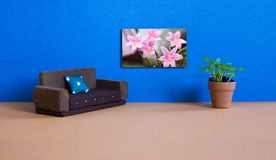 Minimalist living room furniture interior. Simple design brown sofa, flowerpot green plant and spring poster with. Blooming pink flowers Zephyranthes on blue royalty free stock images