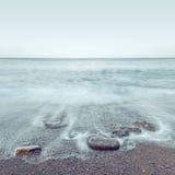 Minimalist misty seascape with rocks Stock Photo