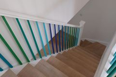 Minimalist Oak staircase, with blue, turquoise and green ombre painted stair spindles. stock photos