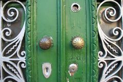 Green door with decorative elements. Minimalist photo of a door painted green with decorations Royalty Free Stock Photo