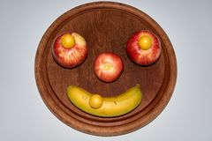 Minimalist round fruit face made of apple, peach and banana stock image