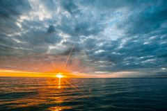 Overcast clouds over calm ocean waters at sunset. Minimalist seascape - overcast clouds over calm ocean waters at sunset Royalty Free Stock Photo
