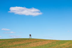 Minimalist spring landscape with field and hunting hide Stock Photography