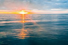 Minimalist sunset over calm ocean water. Minimalist sunset over calm ocean water with orange glare Stock Photography