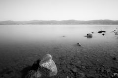Minimalist view of rocks in a lake. A minimalist, long exposure photo of some rocks in a lake, with perfectly still water and empty sky Stock Images