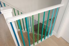 Minimalist wooden staircase with spindles painted in green, turquoise and blue ombre colours. royalty free stock photos