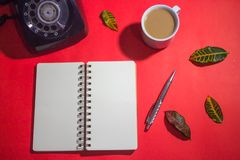 Minimalist workspace on top view with copy space. A cup of coffee, blank notebook, classic phone ,silver pen on red background Royalty Free Stock Image