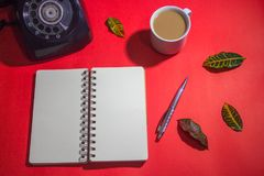 Minimalist workspace on top view with copy space. A cup of coffee, blank notebook, classic phone ,silver pen on red background Stock Photography