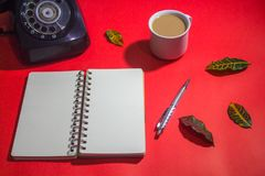 Minimalist workspace on top view with copy space. A cup of coffee, blank notebook, classic phone ,silver pen on red background Stock Photo