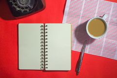 Minimalist workspace on top view with copy space. A cup of coffee, blank notebook, classic phone ,silver pen on red background Stock Images