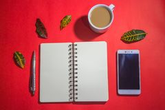 Minimalist workspace on top view with copy space. A cup of coffee, blank notebook, classic phone ,silver pen on red background Royalty Free Stock Photos