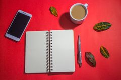 Minimalist workspace on top view with copy space. A cup of coffee, blank notebook, classic phone ,silver pen on red background Stock Photos