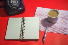 Minimalist workspace on top view with copy space. A cup of coffee, blank notebook, classic phone ,silver pen on red background Royalty Free Stock Photo