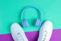 minimalista Mi?o?nik Muzyki He?mofony, biali sneakers na purpurach wybijaj? monety t?o Odg?rny widok Mieszkanie nieatutowy zdjęcia royalty free