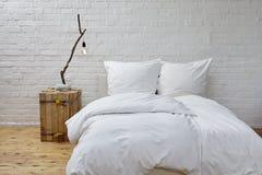 Minimalistic卧室白色亚麻布和分支灯 免版税库存图片