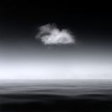 Minimalistic abstract landscape of a single cloud over a smooth sea, B&W.  stock photo