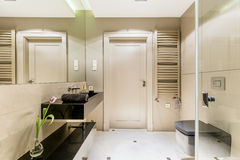 Minimalistic bathroom with a black sink. Shot of a minimalistic bathroom interior with a black polished sink stock image