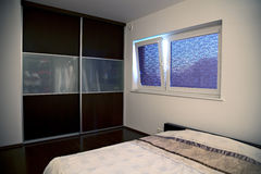Minimalistic bedroom with big built-in cabinet. Minimalistic bedroom in light tones with big built-in cabinet and functional roller blinds Stock Photo